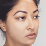 three quarter view of a woman's face who has have eyebrow tattoos